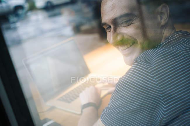 Homme souriant utilisant un ordinateur portable dans un café — Photo de stock