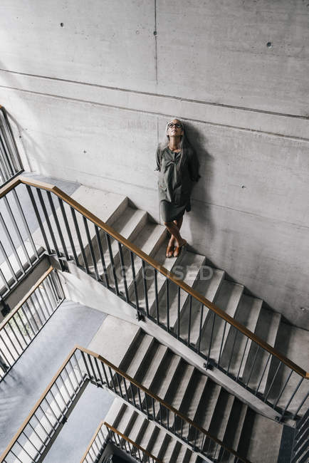 Woman with long grey hair leaning against wall in office — Stock Photo