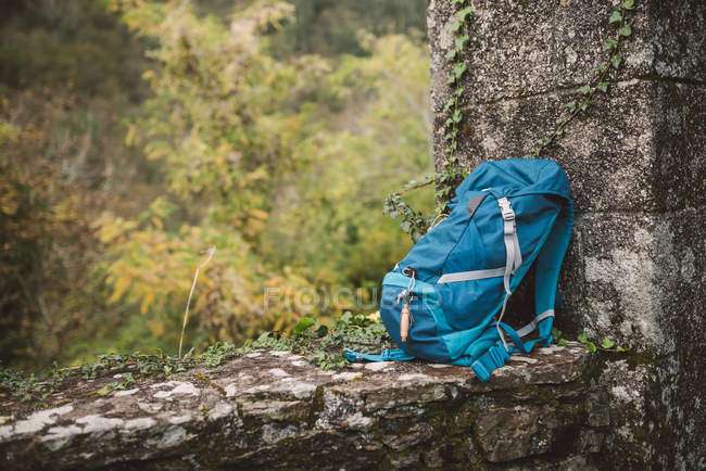 Blue backpack on a stone wall in nature — Stock Photo