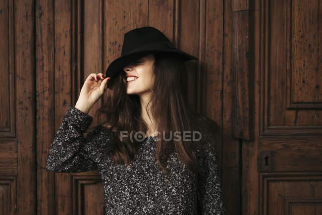 Sorridente giovane donna in piedi davanti alla porta di legno che copre gli occhi con il cappello — Foto stock