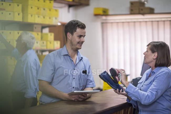 Uomo in magazzino con scatole di scarpe che parla con il cliente — Foto stock