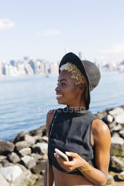 Sonriente joven mujer de pie con el teléfono celular en el paseo marítimo - foto de stock
