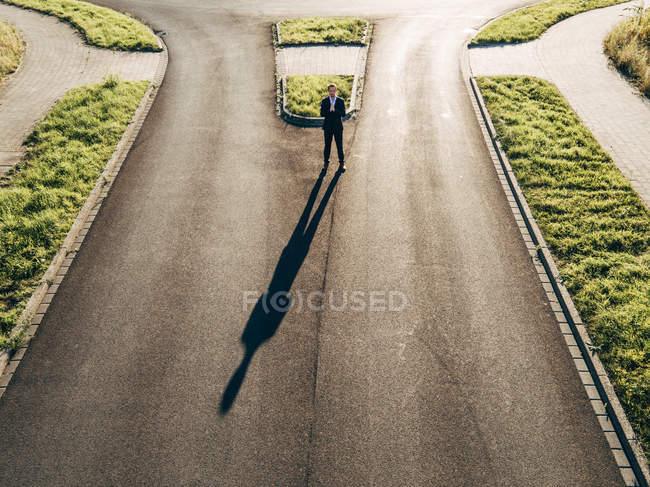Сосредоточенный бизнесмен, стоящий на дороге под солнцем — стоковое фото