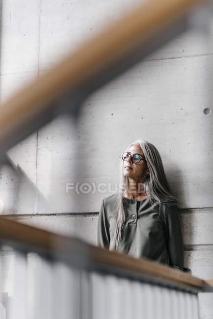 Femme aux longs cheveux appuyé contre le mur sur escalier — Photo de stock