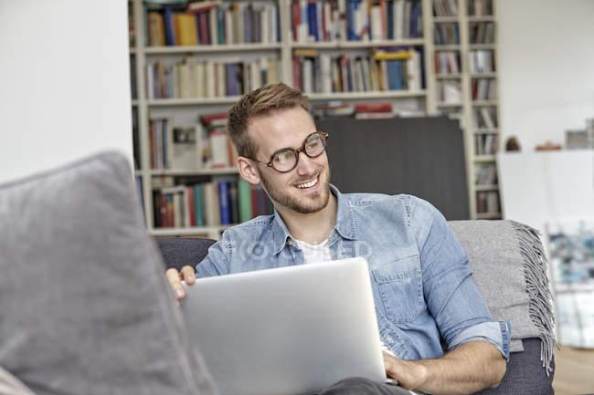 Retrato de homem sorridente sentado com laptop em casa — Fotografia de Stock