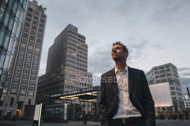 Улыбающийся бизнесмен, стоящий вечером на Потсдамской площади — стоковое фото