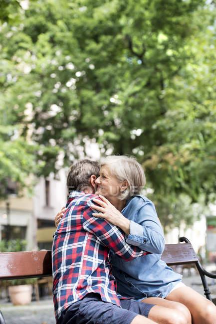 Счастливая старшая пара обнимает друг друга на скамейке в парке — стоковое фото
