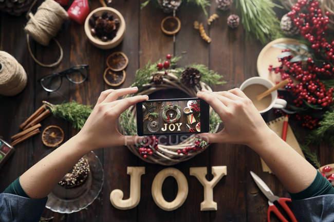 Frauenhände fotografieren selbstgebastelten Adventskranz mit Smartphone — Stockfoto