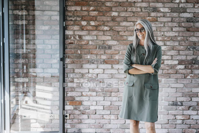 Smiling woman with long grey hair standing in front of brick wall — Stock Photo