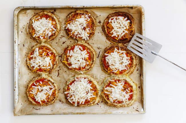 Homemade glutenfree mini pizzas with cauliflower and pumpkin on baking tray — Stock Photo