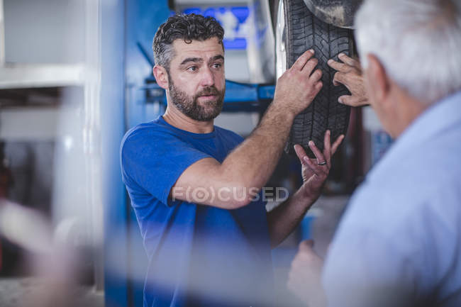Car mechanic in workshop with male customer — Stock Photo