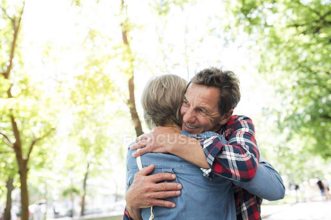 Felice coppia anziana carino abbracciare al parco — Foto stock