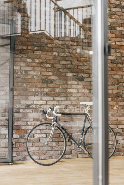 Bicycle placed at brick wall in office — Stock Photo