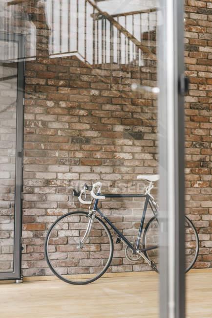 Biciclette messo al muro di mattoni in ufficio — Foto stock