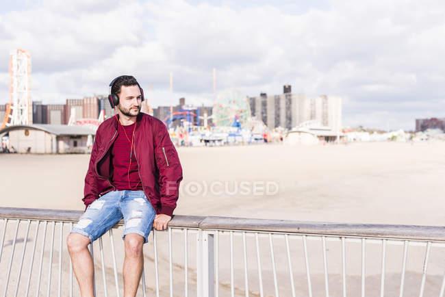 Man sitting on railing on Coney Island wearing headphones, New York City, USA — Stock Photo