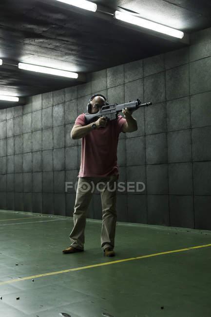 Homem, mirando com uma arma tática em um campo de tiro indoor — Fotografia de Stock