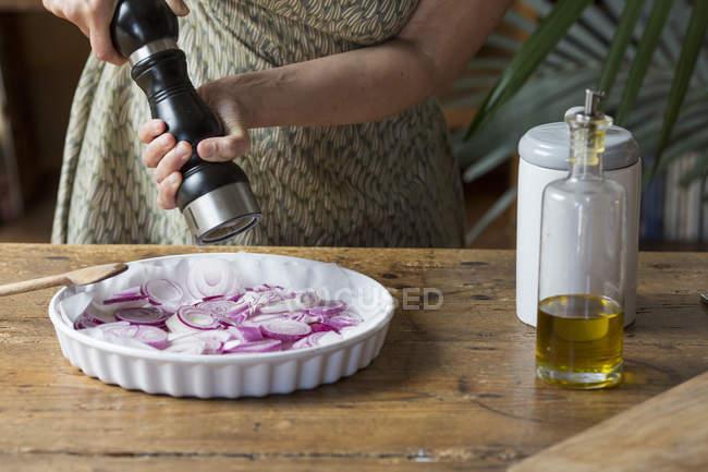 Жінка готує червоним цибулею для цибулі песто додавання солі — стокове фото
