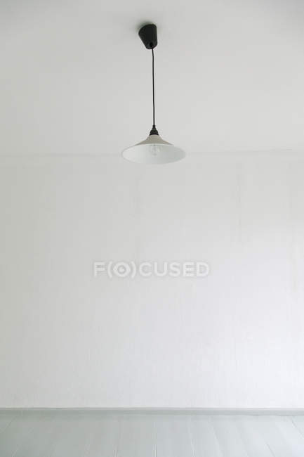 Ceiling lamp in white empty room — Stock Photo