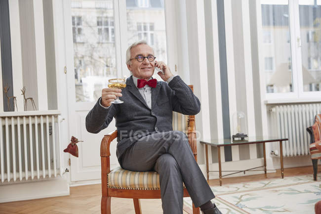 Smiling senior man on the phone sitting on chair with champagne glass — Stock Photo