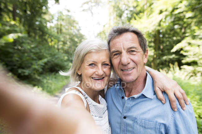 Active cute senior couple taking selfie in park — Stock Photo