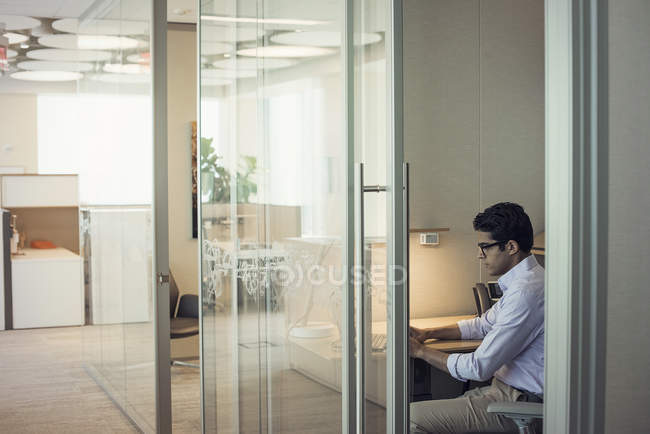 Focused businessman using laptop in office — Stock Photo