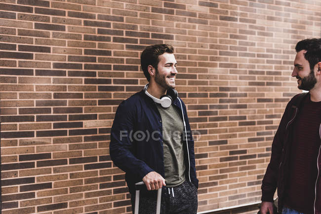 Two smiling friends with trolley bag talking in front of brick wall — Stock Photo
