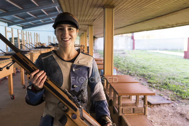 Retrato de uma mulher sorridente segurando seu rifle esportivo em um campo de tiro — Fotografia de Stock