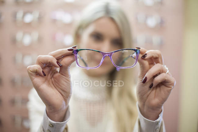 Blond woman selecting new glasses in opticians shop — Stock Photo