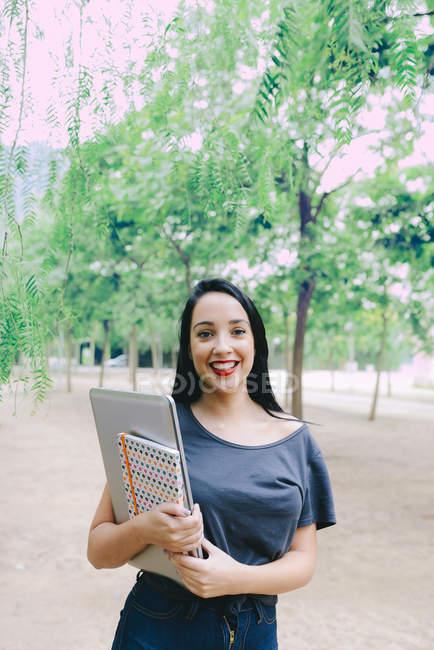Sorrindo jovem segurando um laptop e um notebook ao ar livre — Fotografia de Stock