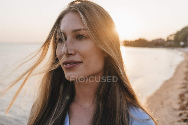 Portrait of young woman on the at sunset — Stock Photo