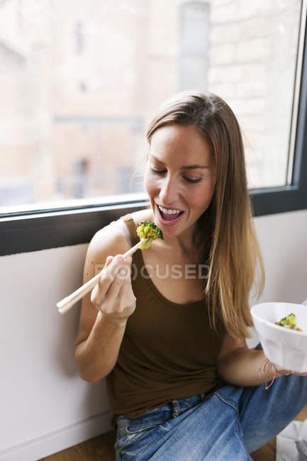 Женщина дома ест овощи палочками — стоковое фото
