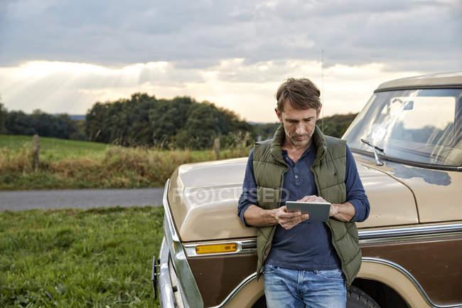 Людина за допомогою планшетного далі до Ван в природі — стокове фото