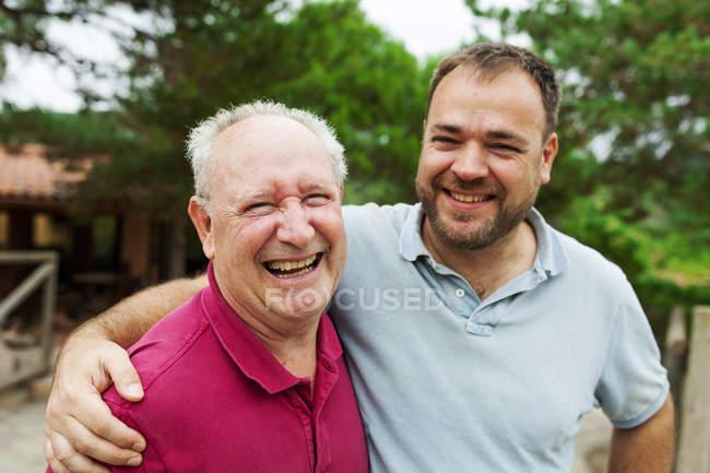 Adulto figlio baci e abbracci vecchio padre all'aperto — Foto stock