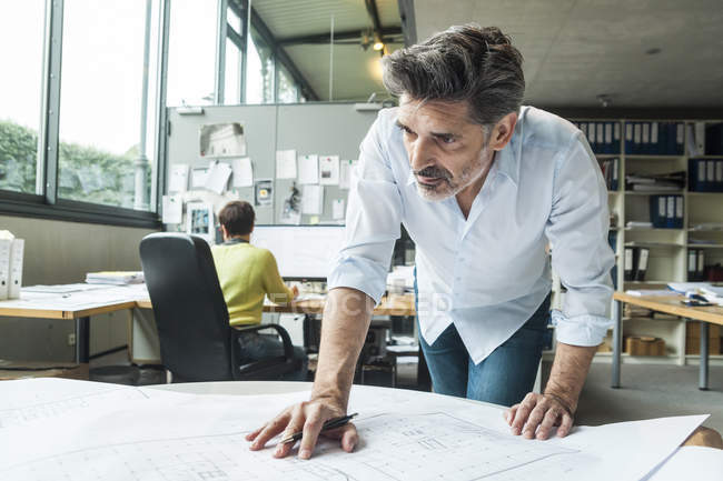 Architect working on ground plan in office with colleague on background — Stock Photo