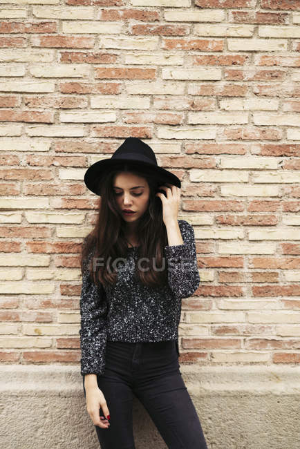 Fashionable young woman wearing black hat standing in front of facade — Stock Photo