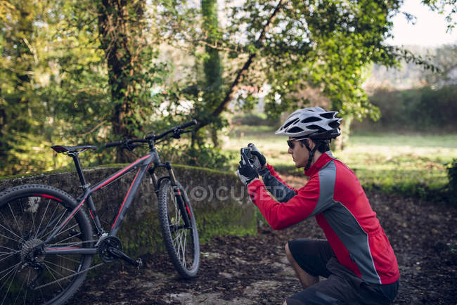 Motociclista maschio scattare foto di mountain bike in natura — Foto stock