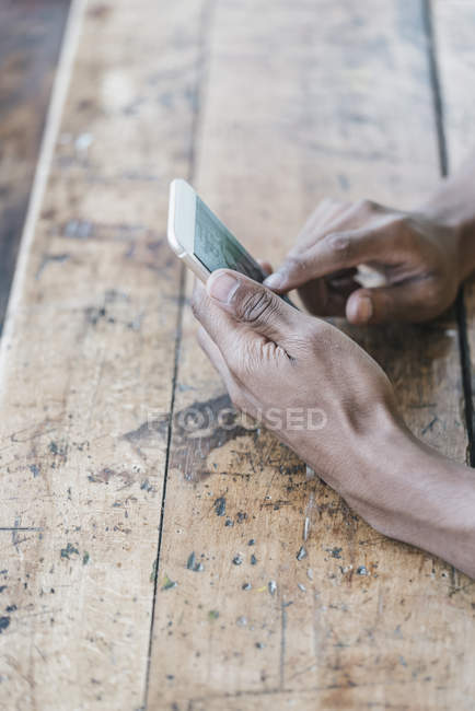 Close-up of Young man using smartphone at shabby wooden table — Stock Photo