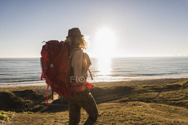 Teenage girl with backpack standing at beach in the evening twilight — Stock Photo