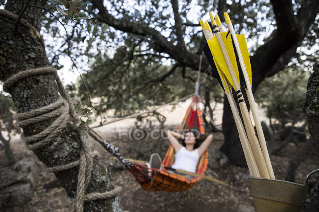 Arrows of an young sporty archeress resting on a hammock in the background — Stock Photo
