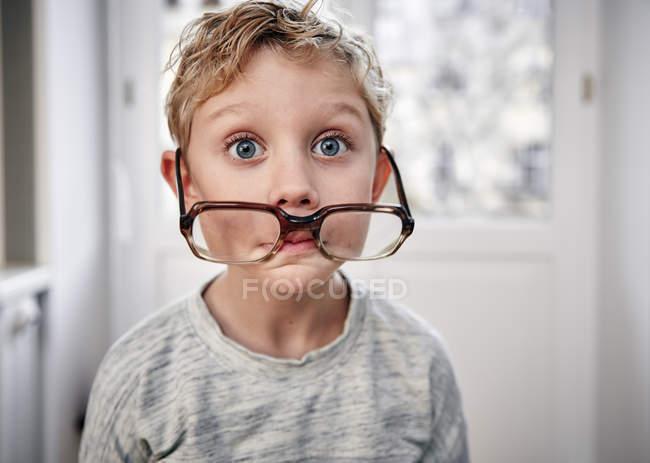 Portrait of playful boy with oversized glasses — Stock Photo