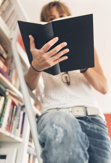 Frau liest ein Buch im Bücherregal — Stockfoto