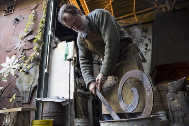 Кузнец за работой в своей мастерской охлаждения металлических деталей — стоковое фото