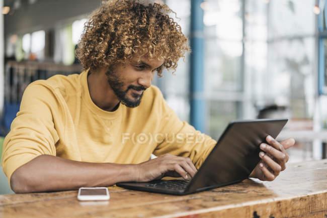 Hombre joven sentado en la mesa y trabajando con el ordenador portátil - foto de stock