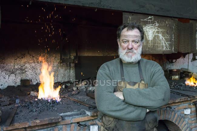 Портрет кузнеца со скрещенными руками в мастерской — стоковое фото