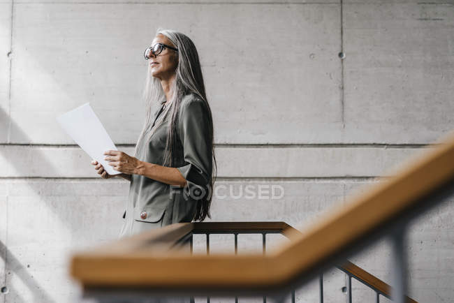 Woman with long grey hair holding document in modern office — Stock Photo