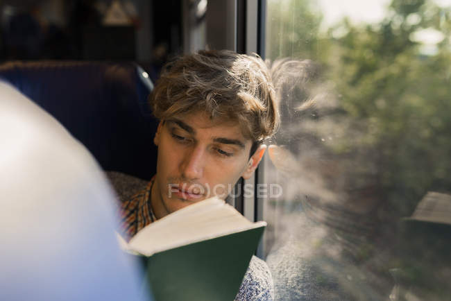 Young man reading book in a train — Stock Photo