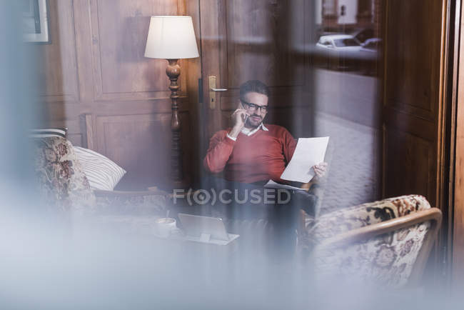 Young man on cell phone looking at document in a cafe — Stock Photo