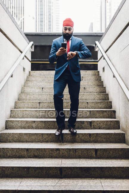 Indischer Geschäftsmann mit Telefon zu Fuß nach unten in manhattan, ny, USA — Stockfoto