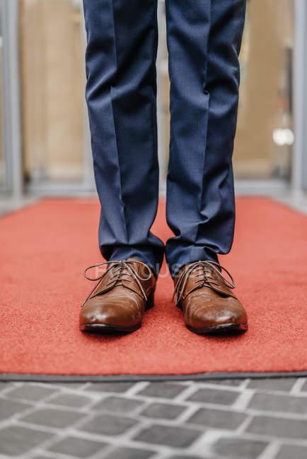 Close-up de pernas de empresário em pé no tapete vermelho — Fotografia de Stock