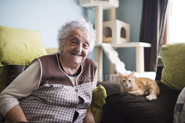 Smiling Senior woman sitting on couch with kitten and looking at camera — Stock Photo